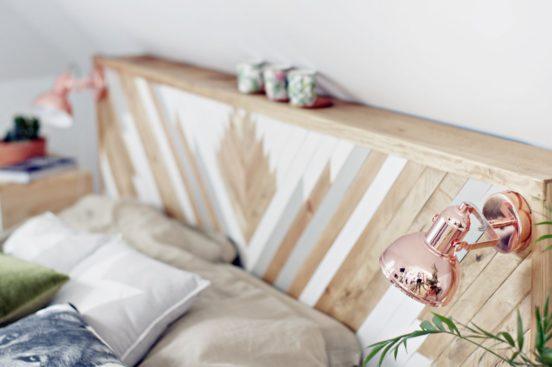 Miedziany kinkiet (Edit BRITOP Lighting) bardzo dobrze pasuje do drewnianej ramy łóżka.